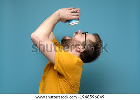 Man is tormented by thirst, he threw back head, opened mouth and pours the last drops from a paper, disposable cup. Early morning.  Foto stock ©