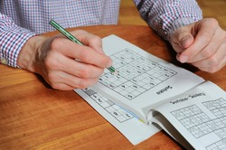 Man is trying to solve a sudoku with a pencil