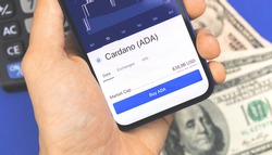 Man is using smartphone for buying Cardano ADA crypto currency, mobile trade and stock exchanges concept background