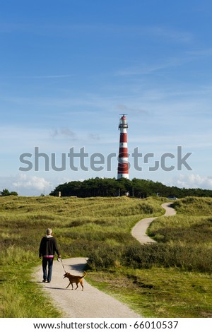Man is walking his dog near the lighthouse