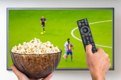 Man is watching football match on TV and holding tv remote controller and popcorn in hands
