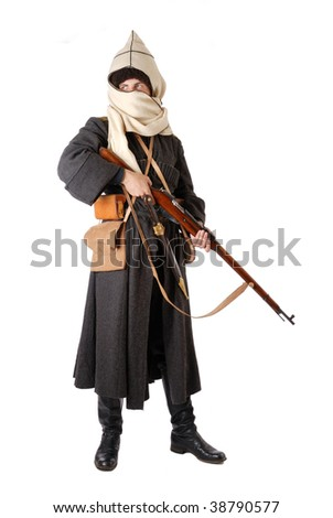 Man is wearing vintage uniform of Russian Cossack in time First World War. Re-enactor is holding rifle. He is dressed in woolen greatcoat, fur-cap and boots. His face is closed with hood.