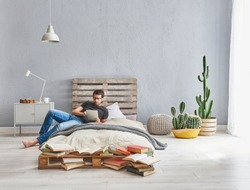 Man is working in the modern bed room. Wooden pallet bed and working from home style. home office decoration.