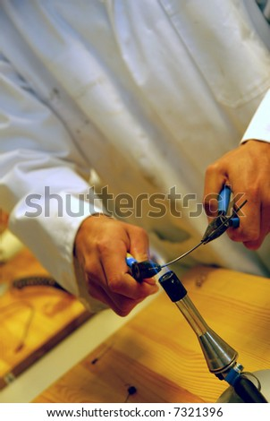 Man is working with bunsen burner. He's wearing a lab coat.