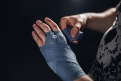 Man is wrapping hands with blue boxing wraps. Isolated on black with red nails. Strong hand and fist, ready for fight and active exercise. Matte wash image.