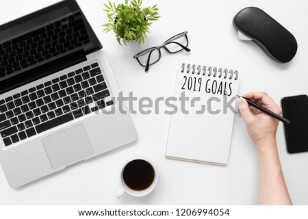 Man is writing 2019 goals on notebook, new year resolutions concept. Top view, flat lay image.