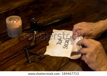 Man is writing on parchment Top Secret and rolls it