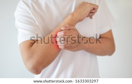 man itching and scratching on arm from itchy dry skin eczema dermatitis Stock photo ©