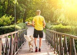 Man jogging across bridge with dog