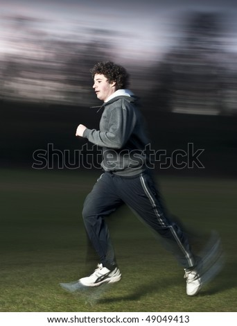 Man jogging in a grassy park, freeze flash and motion blur.