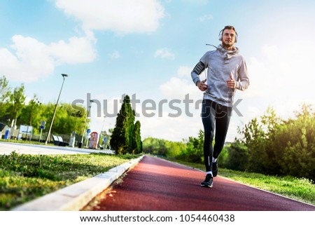 Man jogging in the morning out on the race track #1054460438