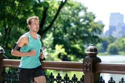 Man jogging in urban city NYC with smartphone armband. Male athlete runner running listening to music playlist on mobile phone app and earphones for workout run in New York's Central Park in summer.