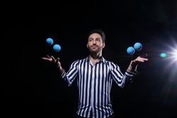 Man juggling blue balls on black background. Stylish Man with black and white shirt posing for the camera.