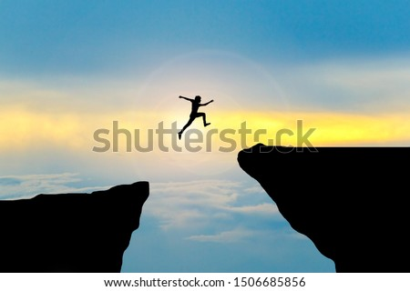 Man jump through the gap between hill.man jumping over cliff Сток-фото ©