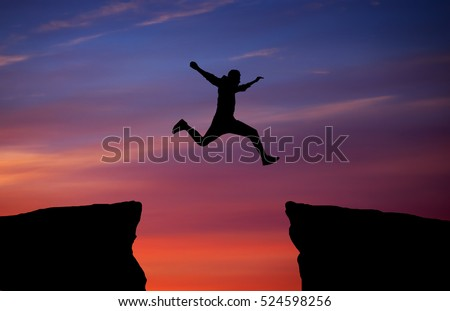 Man jumping across the gap from one rock to cling to the other. Man jumping over rocks with gap on sunset fiery background. Element of design.   #524598256