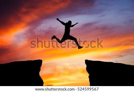 Man jumping across the gap from one rock to cling to the other. Man jumping over rocks with gap on sunset fiery background. Element of design.   #524599567
