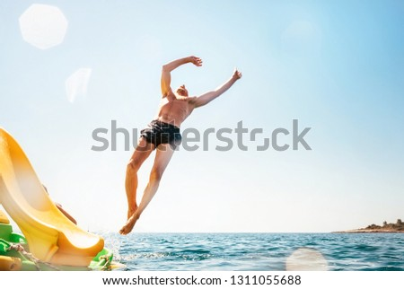 Man jumping backwards somersault into the sea. Happy beach vacation concept image. #1311055688