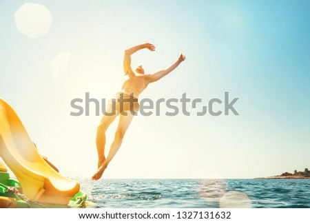 Man jumping backwards somersault into the sea. Happy beach vacation concept image. #1327131632