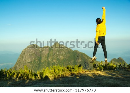 Man Jumping Celebrating Success with the view of a Mountain (Pico Parana - Brazil)