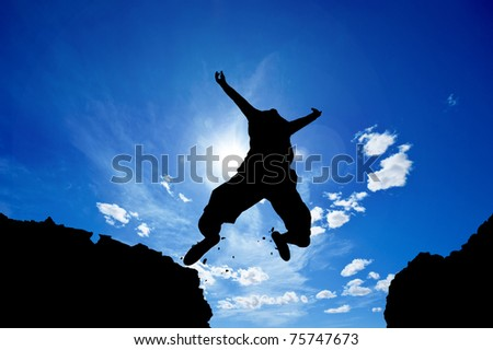 man jumping from a cliff over vivid blue sky