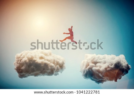 Man jumping from one cloud to another. Taking risks and challenge concept. Overcoming problems, winning.