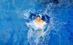 man jumping in pool, huge splash, top view