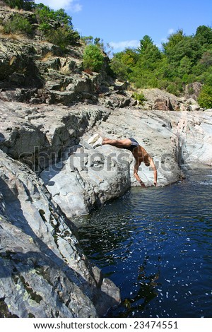 Man jumping into a river from a cliff.