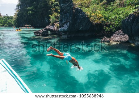 Man jumping into clear sea water in lagoon. Travelling tour in Asia: El Nido, Palawan, Philippines.