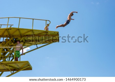Man jumping off a water jumps tower into pool, blurred