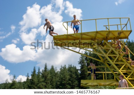 Man, jumping off a water jumps tower into pool, blurred