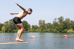 Man jumping off diving board at a public swimming pool