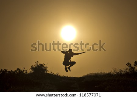 Man jumping on the background of the stunning sunset