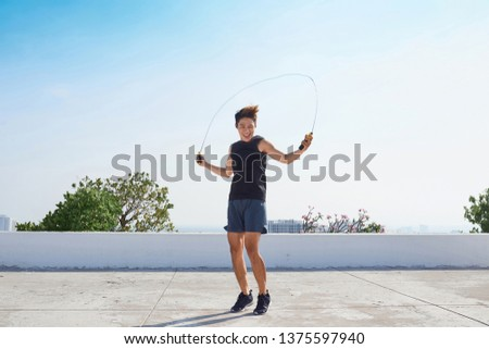 Man jumping on the jumping rope. Young asian descent men with naked torso jumping on the jumping rope outdoors #1375597940