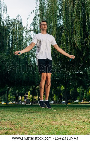 Man jumping on the jumping rope. Young descent men with naked torso jumping on the jumping rope outdoors