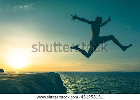 Man jumping over a cliff into the sea on sunset in Koh Phangan island, Thailand. Vintage effect. No fear, courage, brave, dare concept. Three out of three series