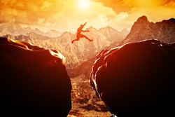 Man jumping over precipice between two rocky mountains at sunset. Freedom, risk, challenge, success.