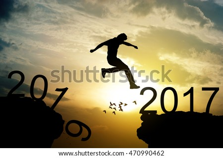 Man jumping over precipice on sunset background , holiday eve calendar happy new year text  2017  concept #470990462