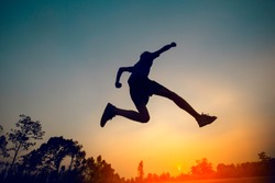 man jumping sunset background
