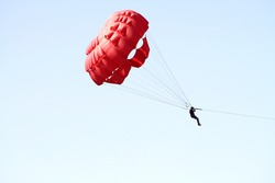 Man jumping with parachute over the blue sky