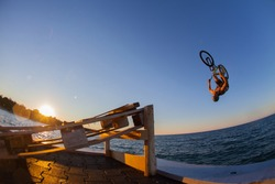 Man jumps a bicycle into the water from a pier