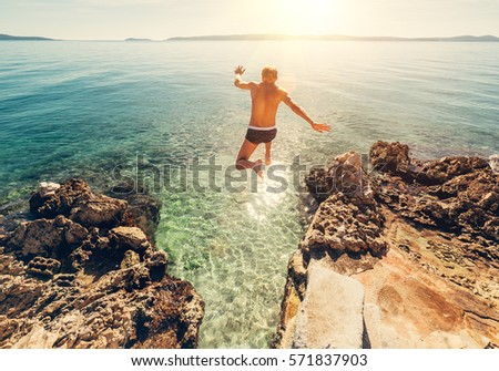 Man jumps in blue sea lagoon water #571837903