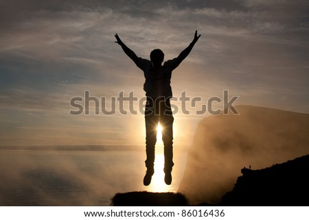 Man jumps into the air at Runde Island (Norway) at sunset.