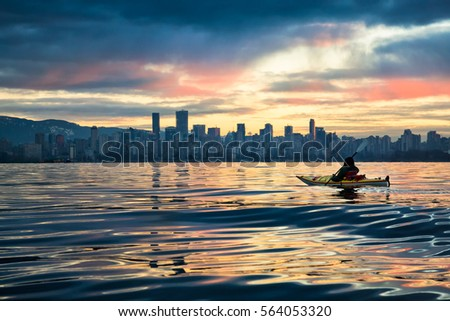 Man kayaking in front of Downtown Vancouver, BC, Canada. Picture taken during a cloudy winter sunrise.