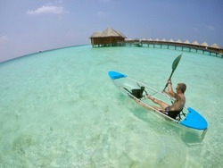 Man kayaking in paradise. Transparent canoe floating on pristine turquoise water, Maldives. Overwater bungalows in the background.