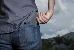 man keeping your wallet in the back pocket of his blue jean sky background