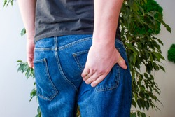 Man keeps hand on lower part of buttocks. Concept photo manifestations of pain at exit of sciatic nerve, inflammation, sciatica or osteochondrosis of spine, pain in gluteus muscle, rectum or anus