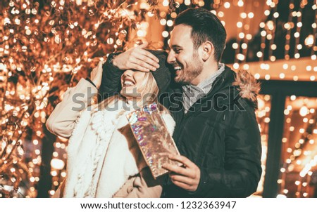 Man keeps his girlfriend eyes covered while she giving a gift for Christmas holiday.