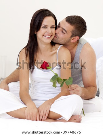 Man kissing a woman and holding a rose in bed