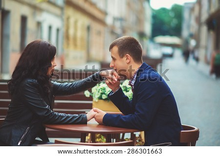 Man kissing a woman\'s hand at a summer cafe