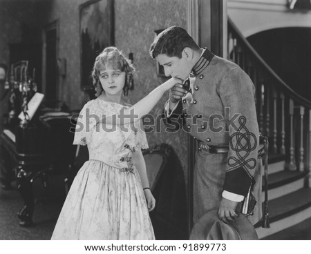 Man kissing hand of woman